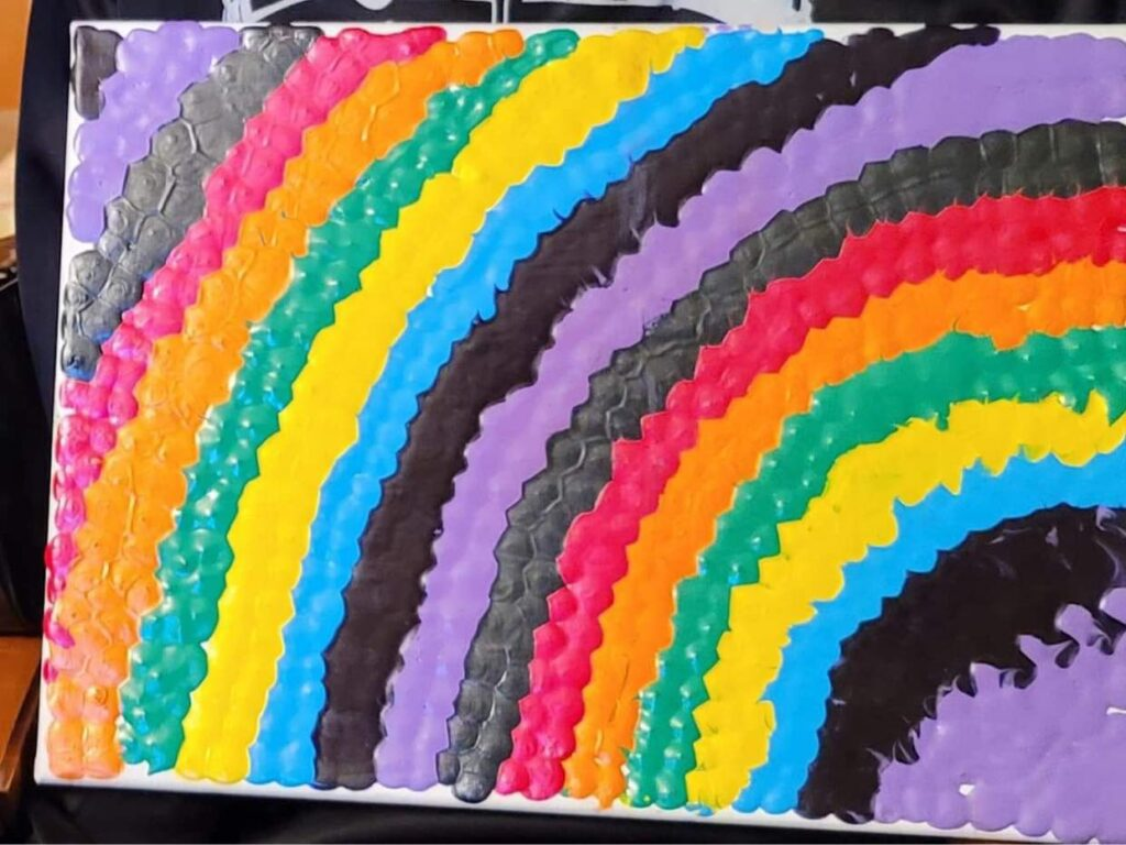 A textured painting on canvas of a rainbow with black stripes intermized with the primary colors
